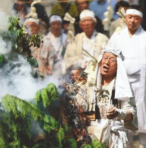 Yoshitsugu Saito chants in front of a fire of saiboku. Saito demonstrated the ritual three times at the local inspection of the world heritage candidate sites by the International Council on Monuments and Sites. Photo: The Yomiuri Shimbun
